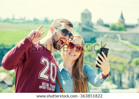 Catching the bright life moments. Beautiful young loving couple taking selfie with smartphone and smiling while traveling by Europe. - stock photo