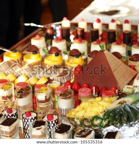 Catering at a luxury event with a wide choice of delicious gourmet desserts displayed on a long buffet table - stock photo