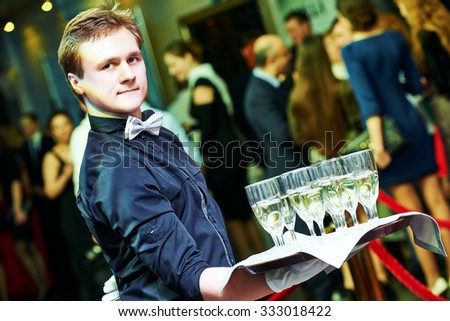 catering or celebration concept. male waiter holding a tray with glasses of vine at party, Authentic shot in mixed light conditions - stock photo