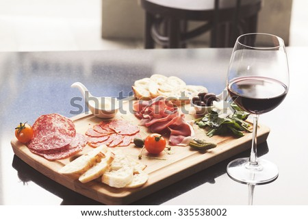 Catering platter with different meat products and red wine on table. - stock photo