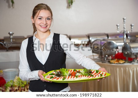 Catering service employee or waitress posing with tray for buffet - stock photo