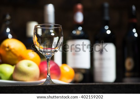 Catering service with one glasses and fruits and alcohol buttles on bartender background - stock photo
