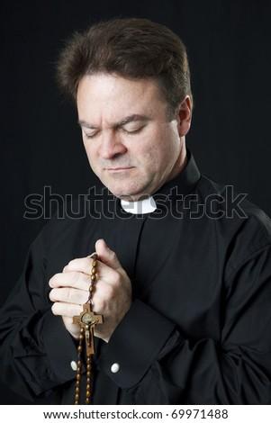 Catholic priest praying with his rosary beads. - stock photo