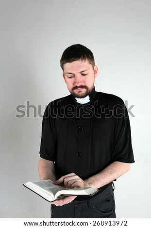 Catholic priest reading book - stock photo