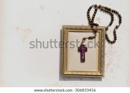 catholic rosary of wood  leaning on frame of gold and paper background - stock photo