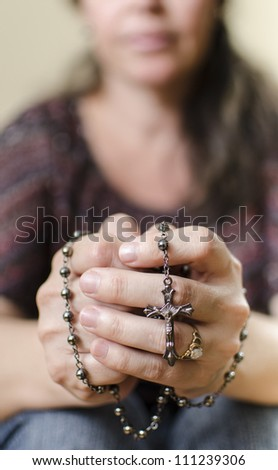 Catholic woman praying with a Rosary