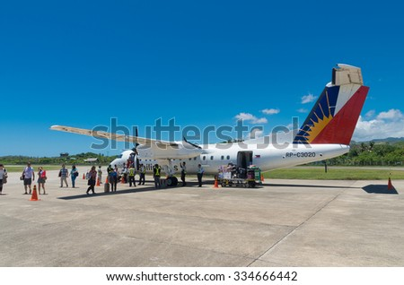 CATICLAN, PHILIPPINES - MAY 13, 2015: Unknown tourists leaving a propeller jet of Philippine Airlines (PAL) . Since July 10, 2013 the airline no longer on the blacklist of the European Union - stock photo
