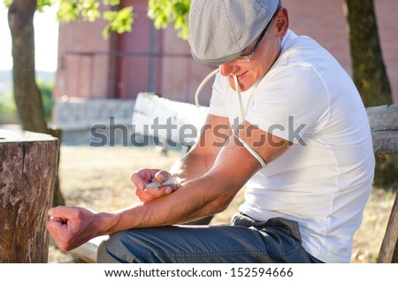 Caucasian addicted man injecting his tied arm intravenously with a dose of soluble heroin in the park - stock photo