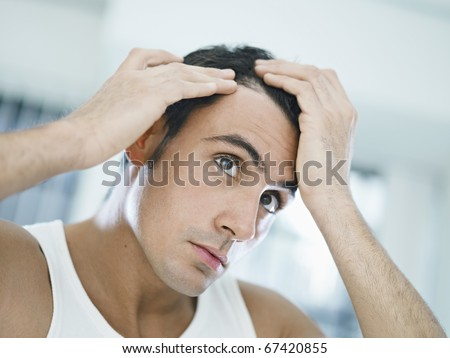 caucasian adult man checking hairline. Horizontal shape, head and shoulders, front view - stock photo