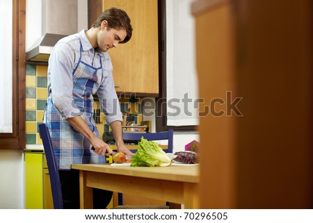 caucasian adult man cutting vegetables in kitchen. Horizontal shape, side view, copy space