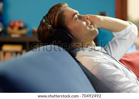 caucasian adult man relaxing on sofa with headphones. Horizontal shape, side view, head and shoulders, copy space