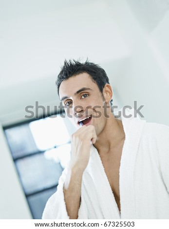 caucasian adult man with bathrobe brushing teeth in bathrooom and looking at camera. Vertical shape, waist up, copy space - stock photo