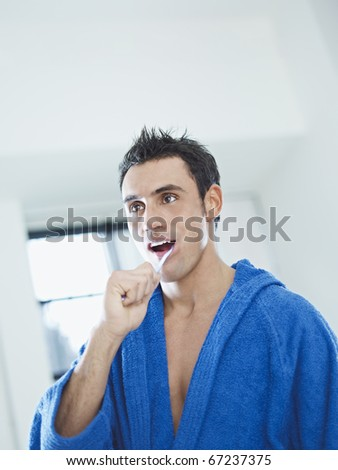 caucasian adult man with bathrobe brushing teeth in bathrooom. Vertical shape, waist up, copy space - stock photo
