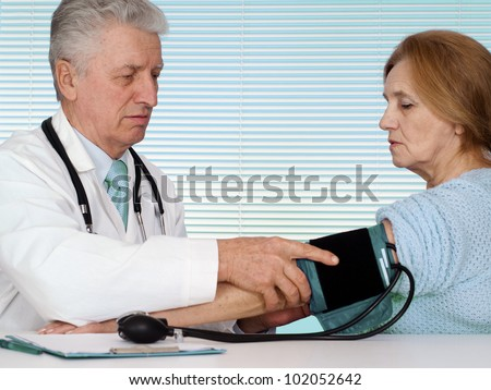 Caucasian aged doctor with a elderly patient on a light background - stock photo