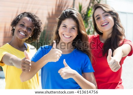 Caucasian and african american girlfriends in colorful shirts showing thumbs in the city with modern buildings and trees in the background - stock photo