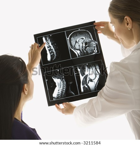Caucasian and Asian Chinese mid-adult female doctors analyzing x-ray. - stock photo
