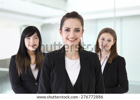 Caucasian and Chinese business women wearing office suits. - stock photo