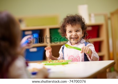 Caucasian and hispanic female preschoolers eating pasta and smiling. Horizontal shape, waist up, focus on background - stock photo