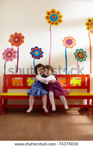 Caucasian and hispanic female preschoolers sitting on bench in kindergarten, playing and smiling. Vertical shape, full length, front view