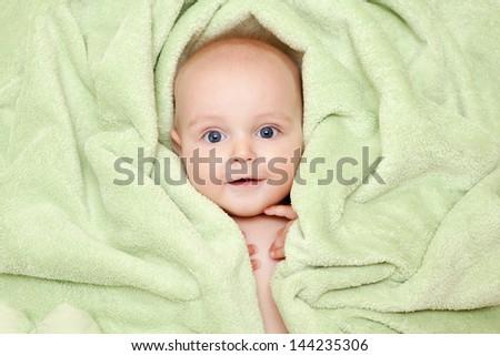 Caucasian baby boy covered with green towel joyfully smiles at camera - stock photo