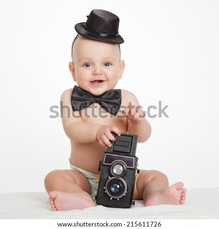 Caucasian baby boy plays with vintage camera an smiles joyfully - stock photo