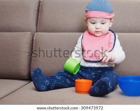 Caucasian baby boy weared bib sitting on braun sofa at home - stock photo