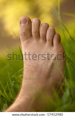 caucasian barefoot in a green grass - stock photo