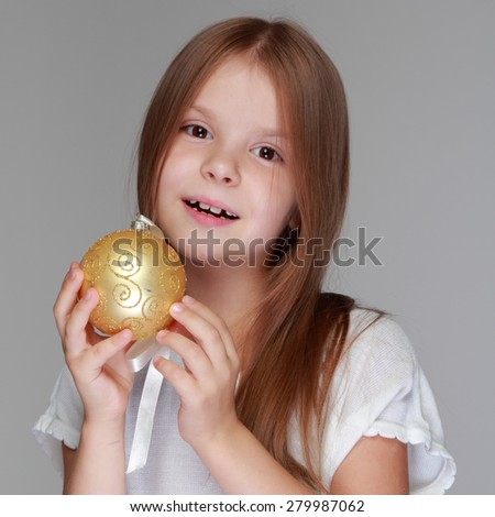 Caucasian beautiful little girl in a white dress holding a Christmas decorative ball for Christmas tree decoration/Smiley girl holding white decorative ball - stock photo