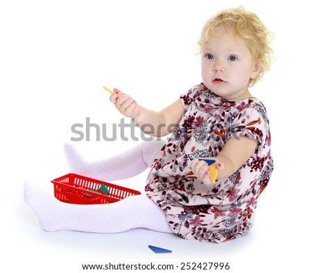 Caucasian beautiful little girl sitting on the floor playing.Isolated on white. - stock photo