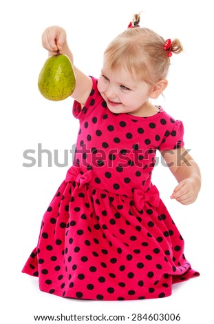 Caucasian blond little girl in a red polka dot dress holding at arm's length pear- isolated on white background - stock photo