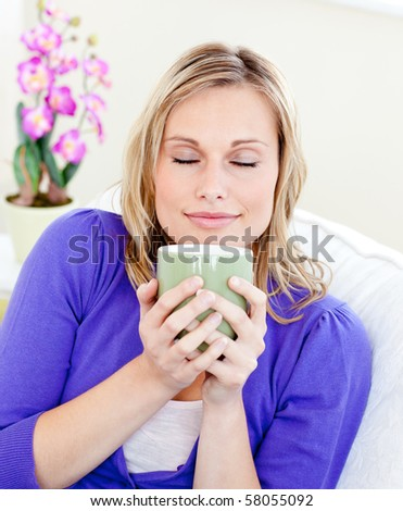 Caucasian blond woman enjoy her coffee sitting on the sofa in the living room