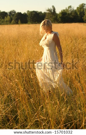 Caucasian blond woman walking in a field of dry grass wearing a vintage dress.