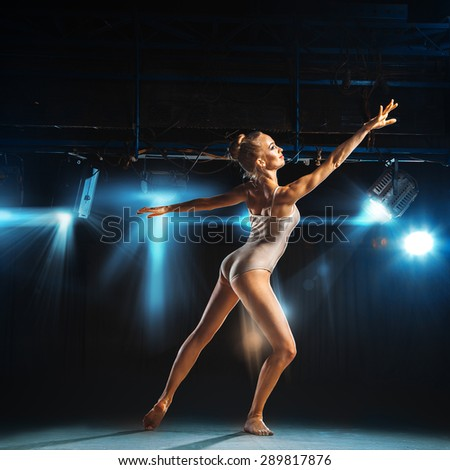 Caucasian blonde ballerina posing on stage in theater - stock photo