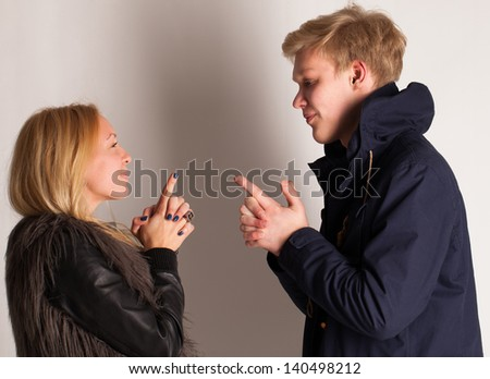 Caucasian blonde couple having fun with fingers up like a guns - stock photo