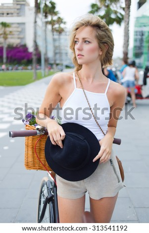 Caucasian blonde hair fashionable female dressed in stylish clothes standing with her vintage bike outdoors, charming woman cyclist resting after riding around the city during the summer holidays - stock photo