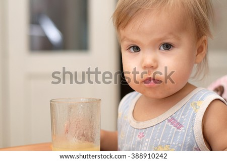 Caucasian blonde little girl eating portrait straight camera looking - stock photo