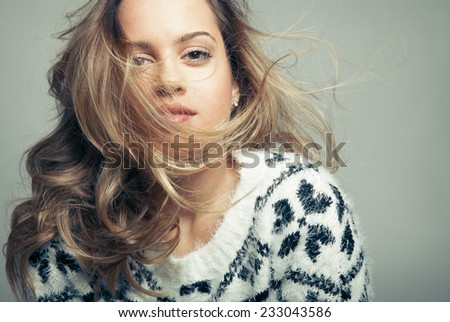 Caucasian blonde model with long wavy hair in the air and perfect light skin. Toned in warm colors, Cosmetics concept, Horizontal shot, studio - stock photo