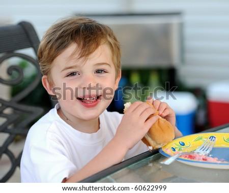Caucasian boy eating hot dog - stock photo