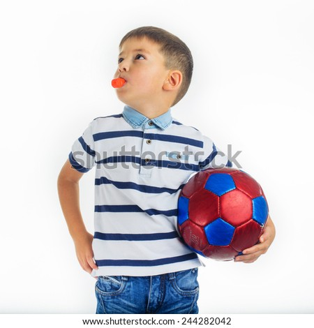 Caucasian boy holding a soccer ball and whistle  - stock photo