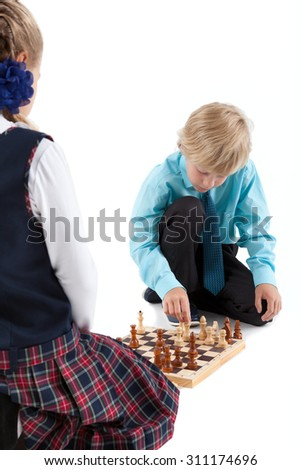 Caucasian boy moving chess figures while playing game with girl, isolated on white background