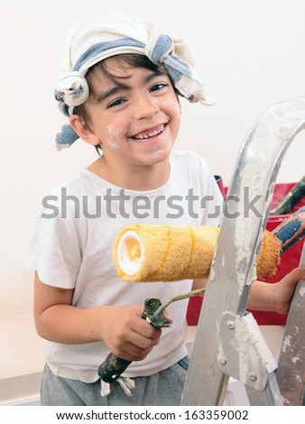 caucasian boy painting and smiling - stock photo