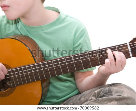 caucasian boy practicing; play acoustic guitar; being bored; isolated on white background - stock photo