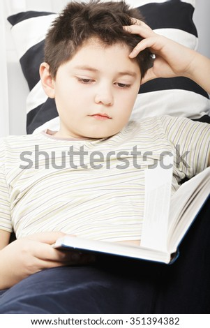 Caucasian boy reading book while laying down on sofa closeup