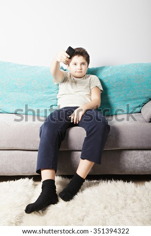 Caucasian boy switching TV channels with remote control while sitting on couch - stock photo