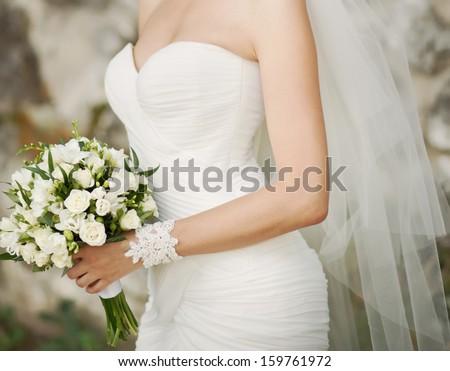 Caucasian bride holding wedding bouquet of various flowers. - stock photo