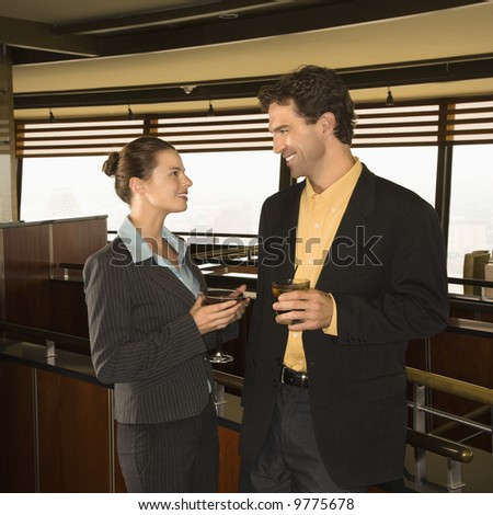 Caucasian business man and woman conversiting with alcoholic beverages.