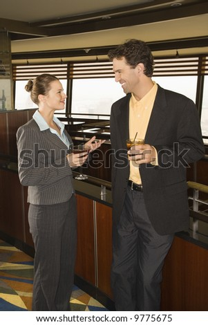 Caucasian business man and woman standing in bar with alcoholic beverages.