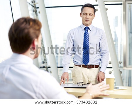 caucasian business manager listening to colleague's explanation during a meeting in office.