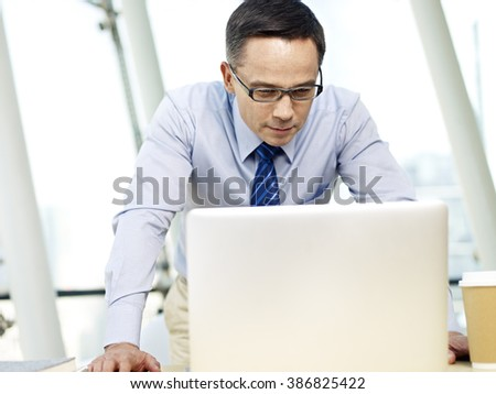 caucasian business people looking at tablet computer in office. - stock photo