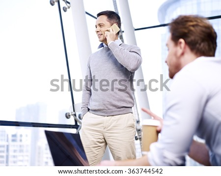 caucasian business people working in office using cellphone and tablet computer. - stock photo